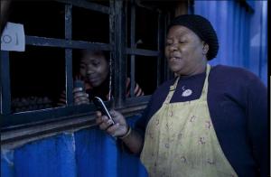Африканская домохозяйка расплачивается в магазинчике